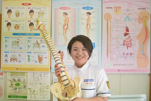 背骨から骨盤までの模型を持ったスタッフ